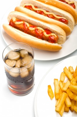 a glass of cola, french fries and three classic hotdogs with mus