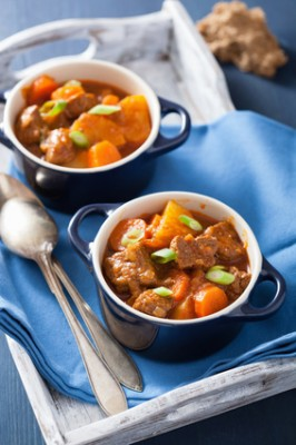 beef stew with potato and carrot in blue pots