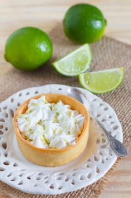 Lemon tart pie on white plate spoone on sackcloth with fresh lim