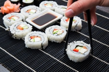 Woman's hand taking philadelphia sushi