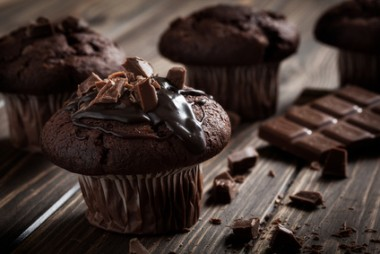 Chocolate muffins with icing and chocolate pieces. Dark lighting